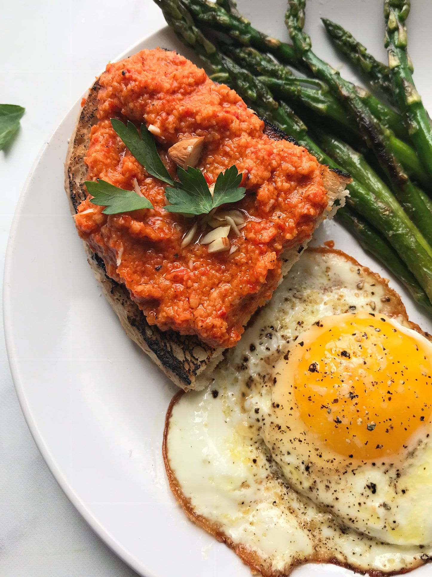 Romesco sauce on toast with egg and asparagus