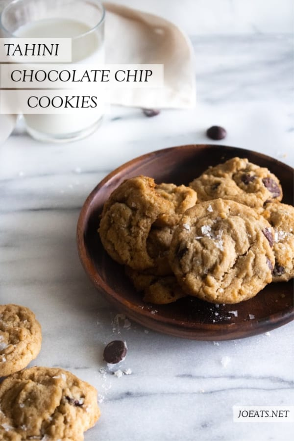 tahini chocolate chip cookies on a wooden plate with milk