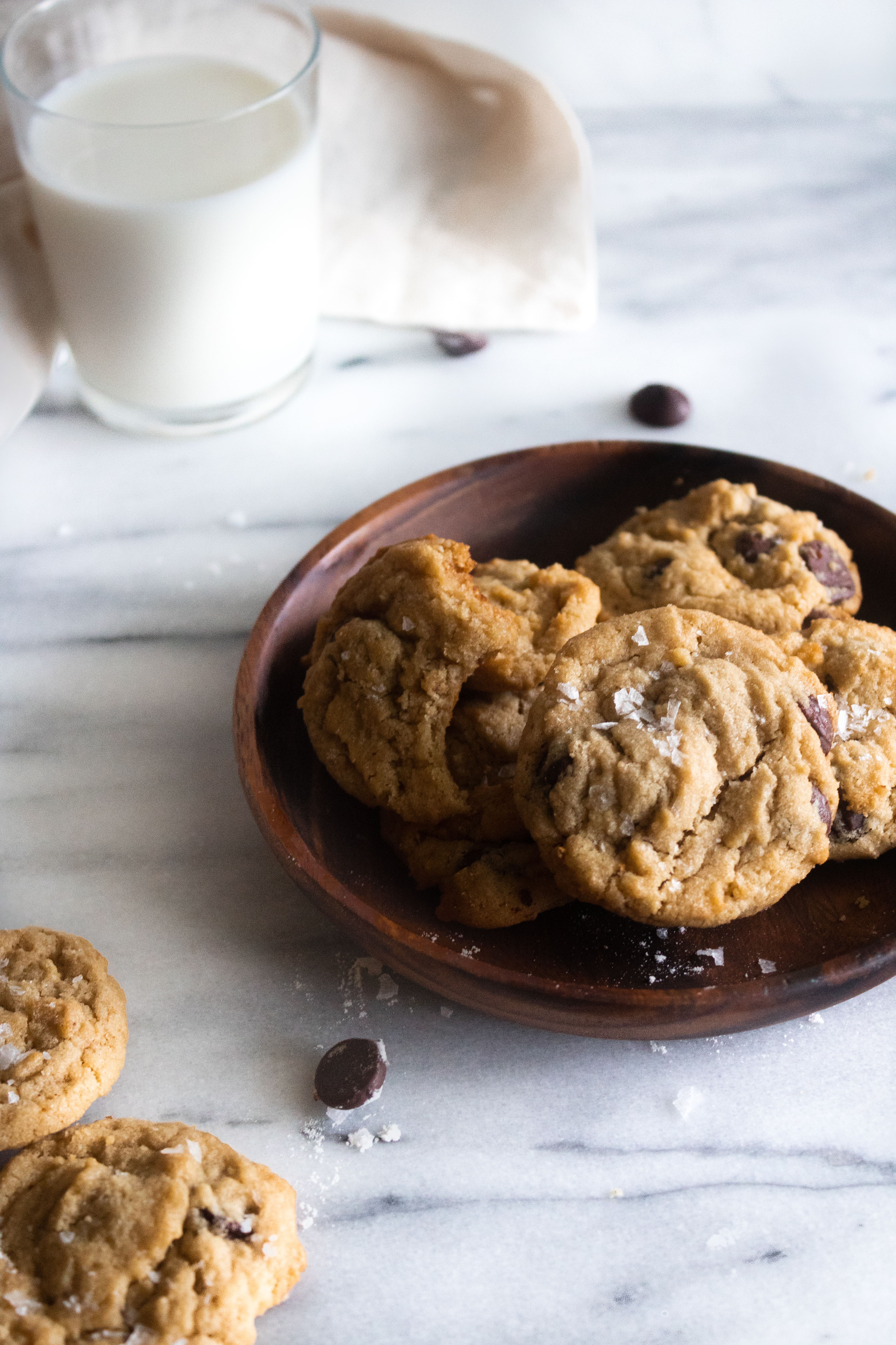 tahini chocolate chip cookies on a wooden plate with a glass of milk