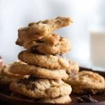 a stack of tahini chocolate chip cookies on a wooden plate
