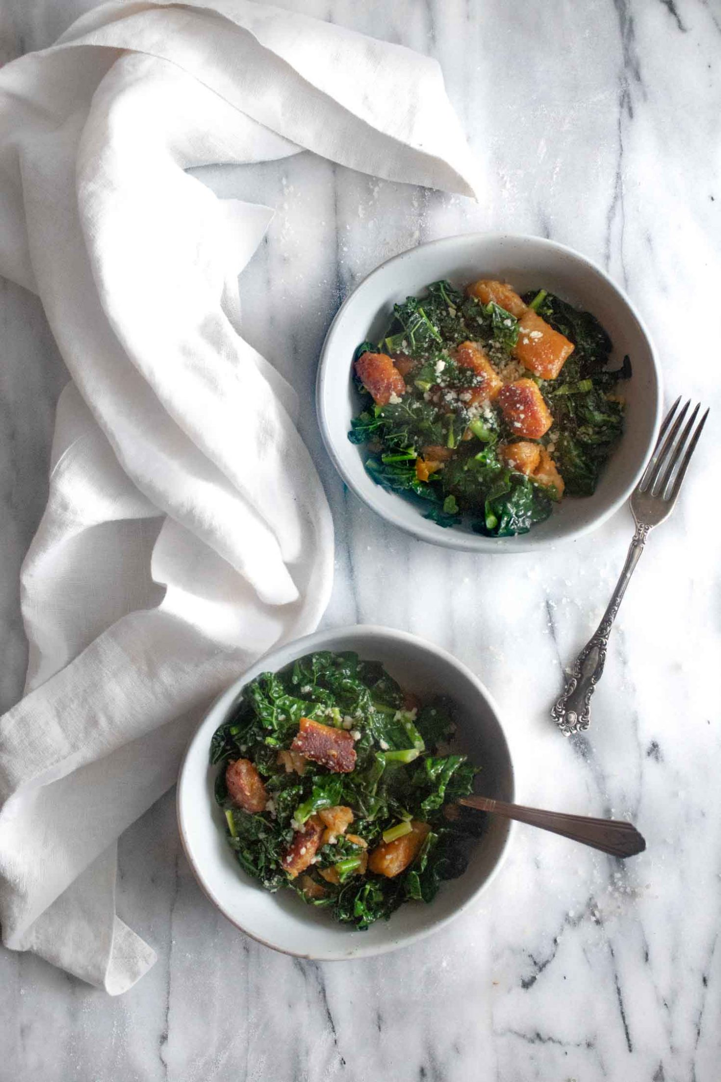 two bowls of sweet potato gnocchi with kale, white napkin, and two forks