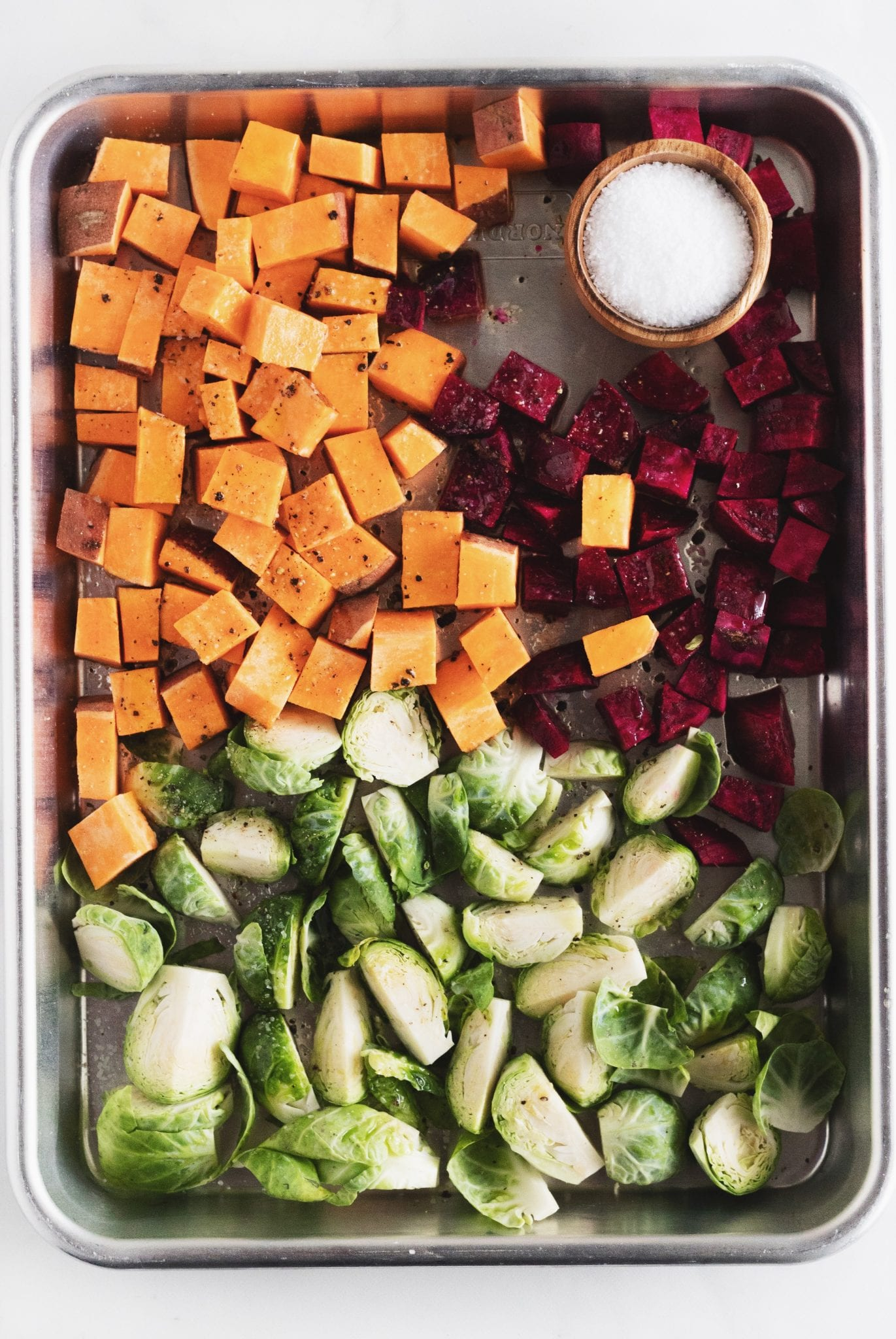 sweet potatoes, beets, and brussel sprouts on a sheet tray with salt