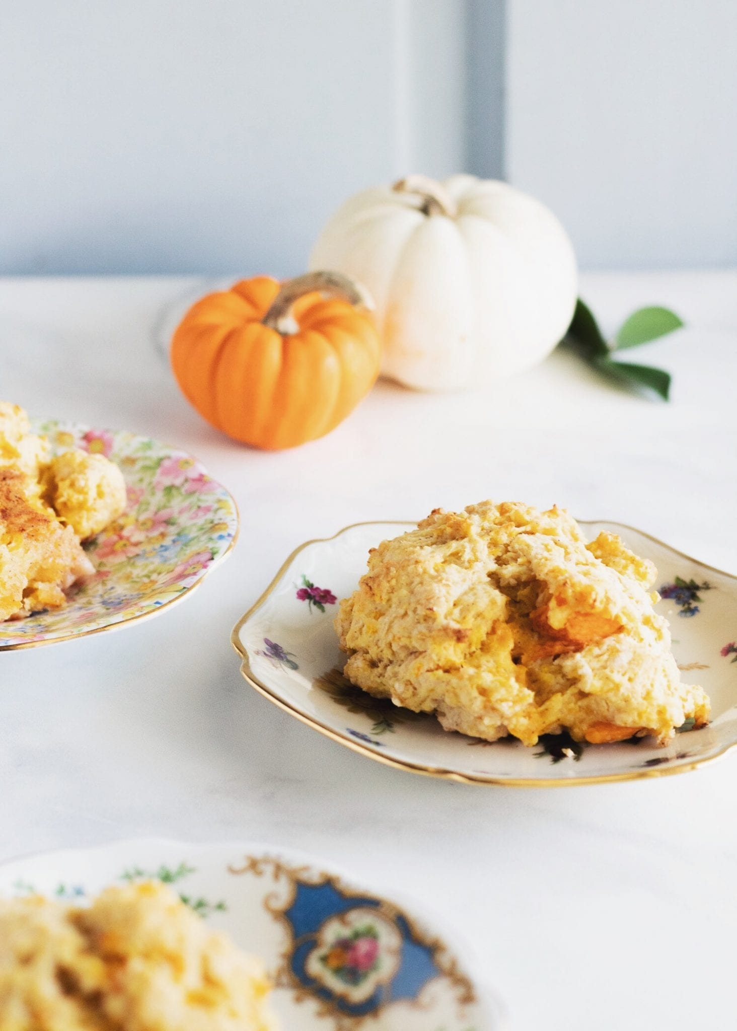 three plates of butternut squash biscuits and two small pumpkins