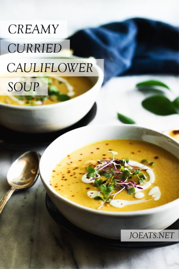 two bowls of curried cauliflower soup with spoon, blue napkin and text overlay