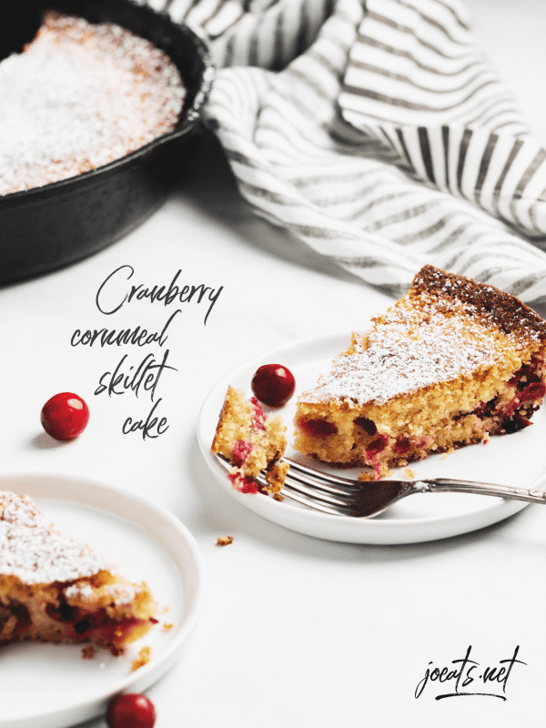 "two plates with cranberry cornmeal cake, iron skillet in background with striped napkin, and scattered cranberries on white background with text overlay that says ""cranberry cornmeal skillet cake"" ""Joeats.net"""