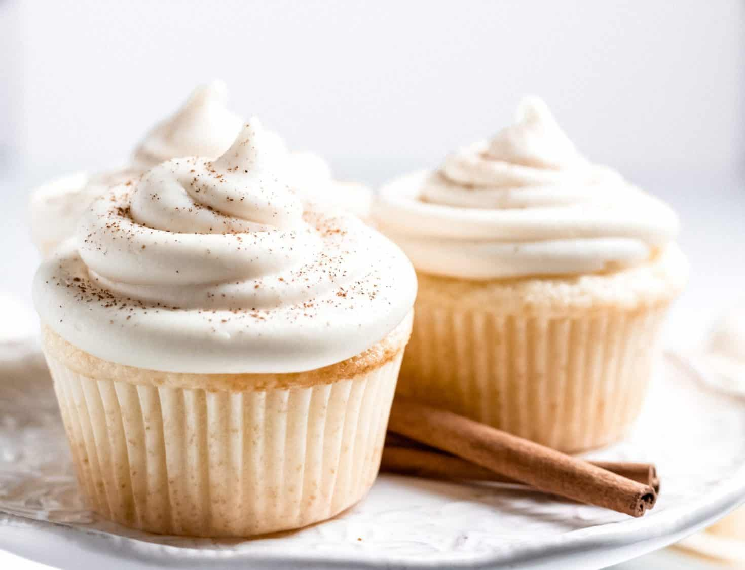 three vanilla buttermilk cupcakes with maple cream cheese frosting and two cinnamon sticks