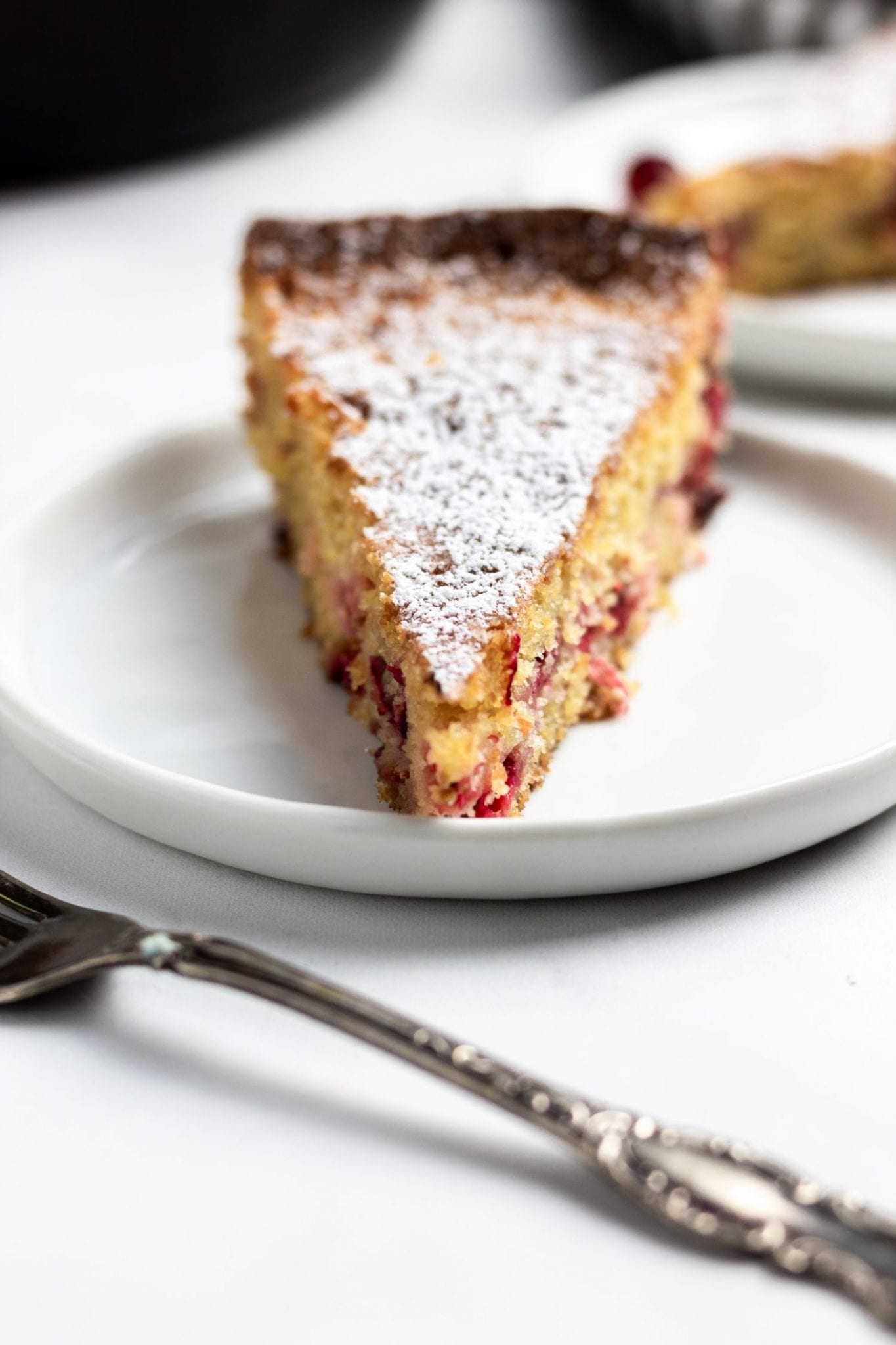 close up shot of slice of cranberry cornmeal cake on a while plate and background with a fork