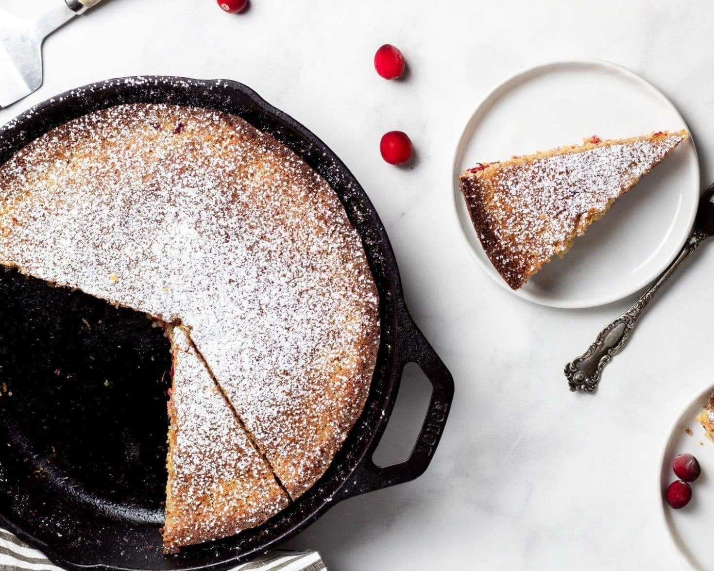 Overhead shot of cast iron skillet with cranberry cornmeal cake with a few slices missing. White plate with slice of cake and fork. Scattered cranberries on white background