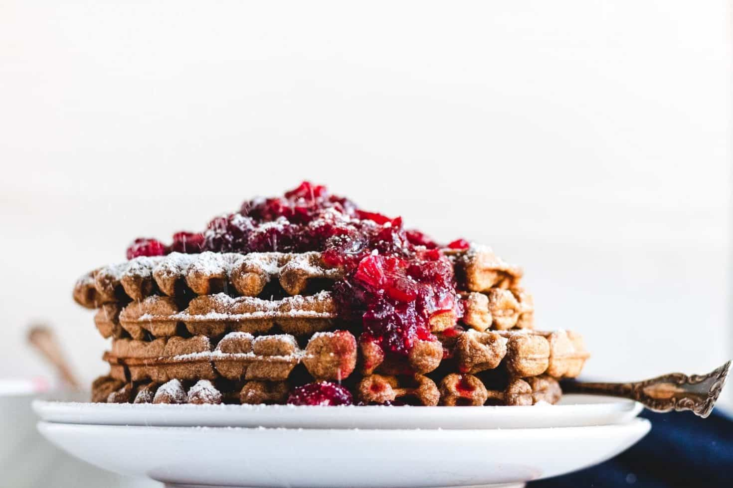 stack of gingerbread waffles with cranberry maple compote and powdered sugar