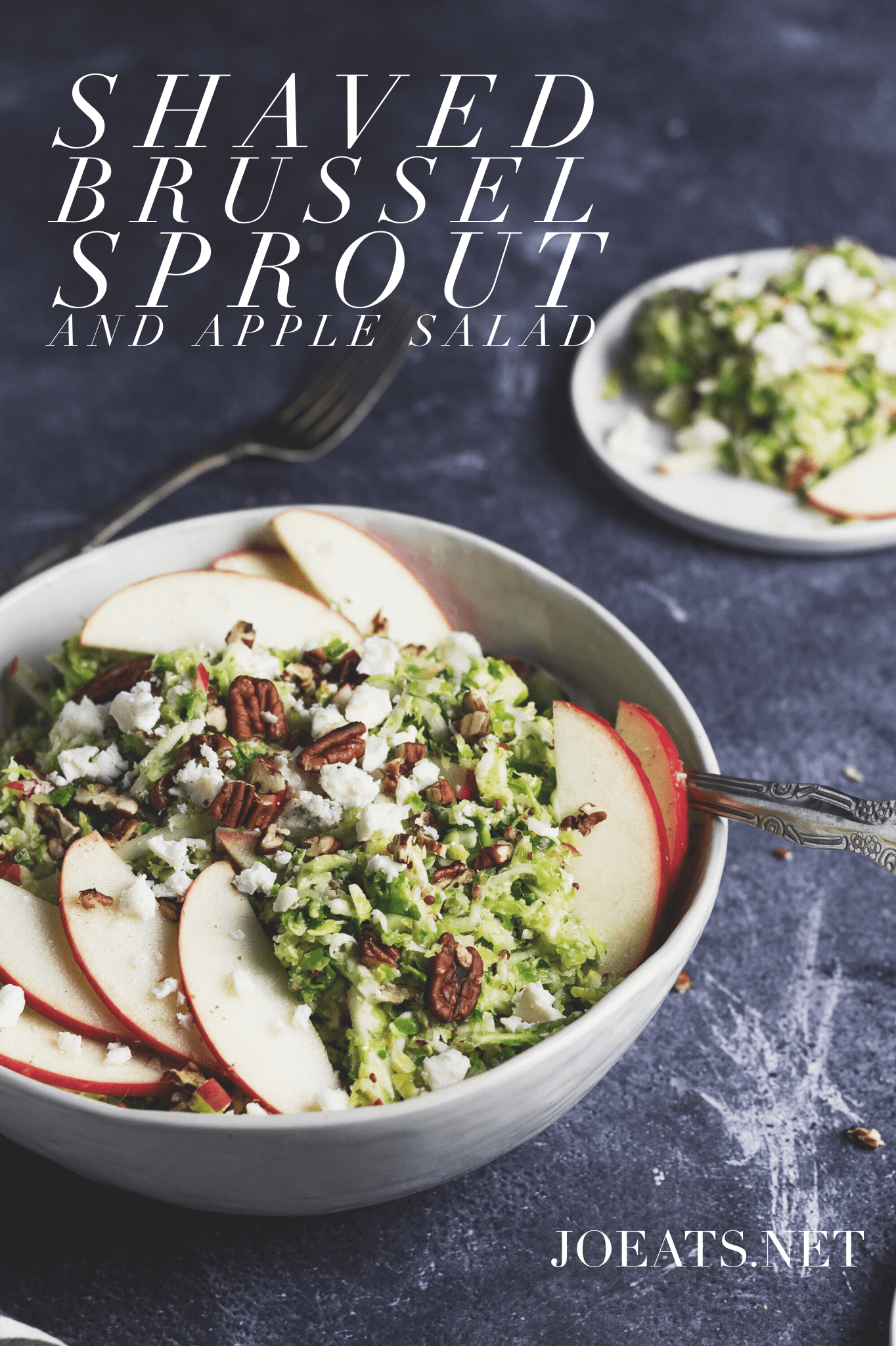 Brussel sprout and apple salad with pecans and blue cheese in a serving bowl. Small white plate with salad in the background and fork, with text overlay