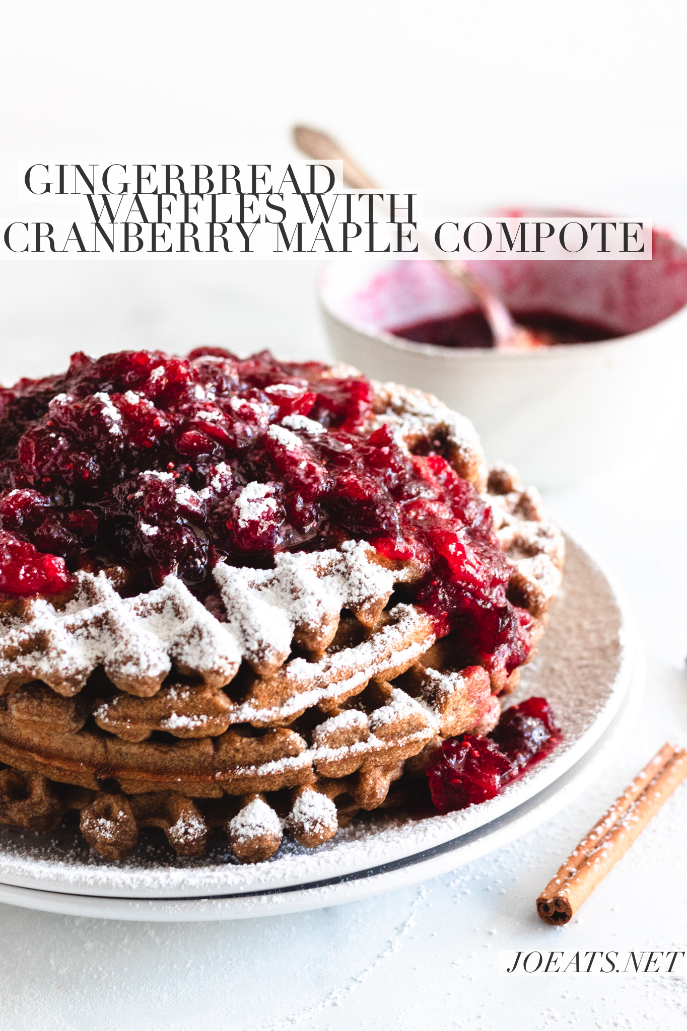 stack of gingerbread waffles with cranberry maple compote and powdered sugar with text overlay