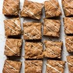 overhead shot of 16 caramelized white chocolate blondies drizzled with melted white chocolate