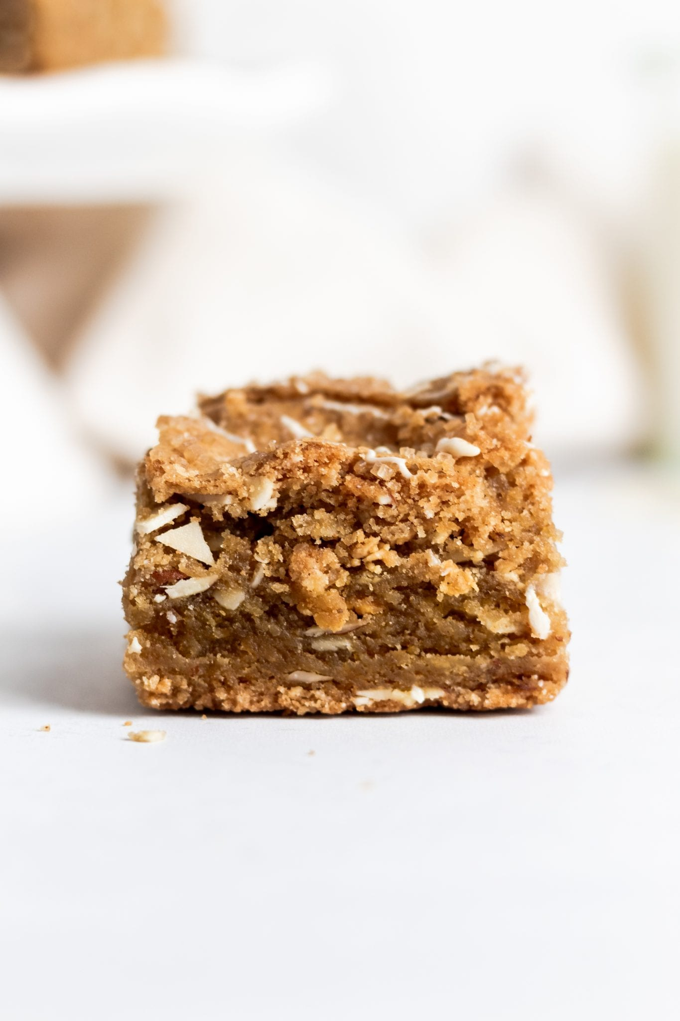 close up of a caramelized white chocolate blondie on a white background