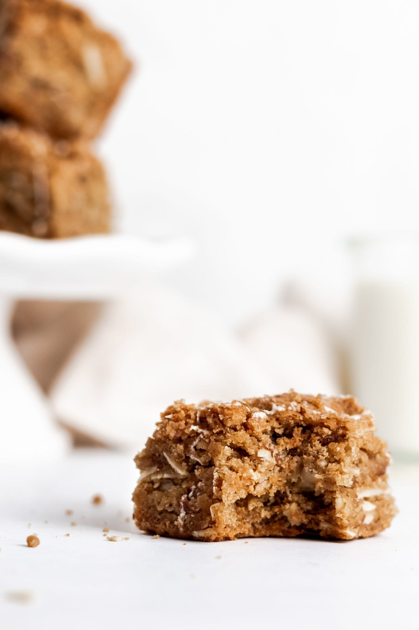 close up of caramelized white chocolate and almond blondie on a white background with a bite taken out.