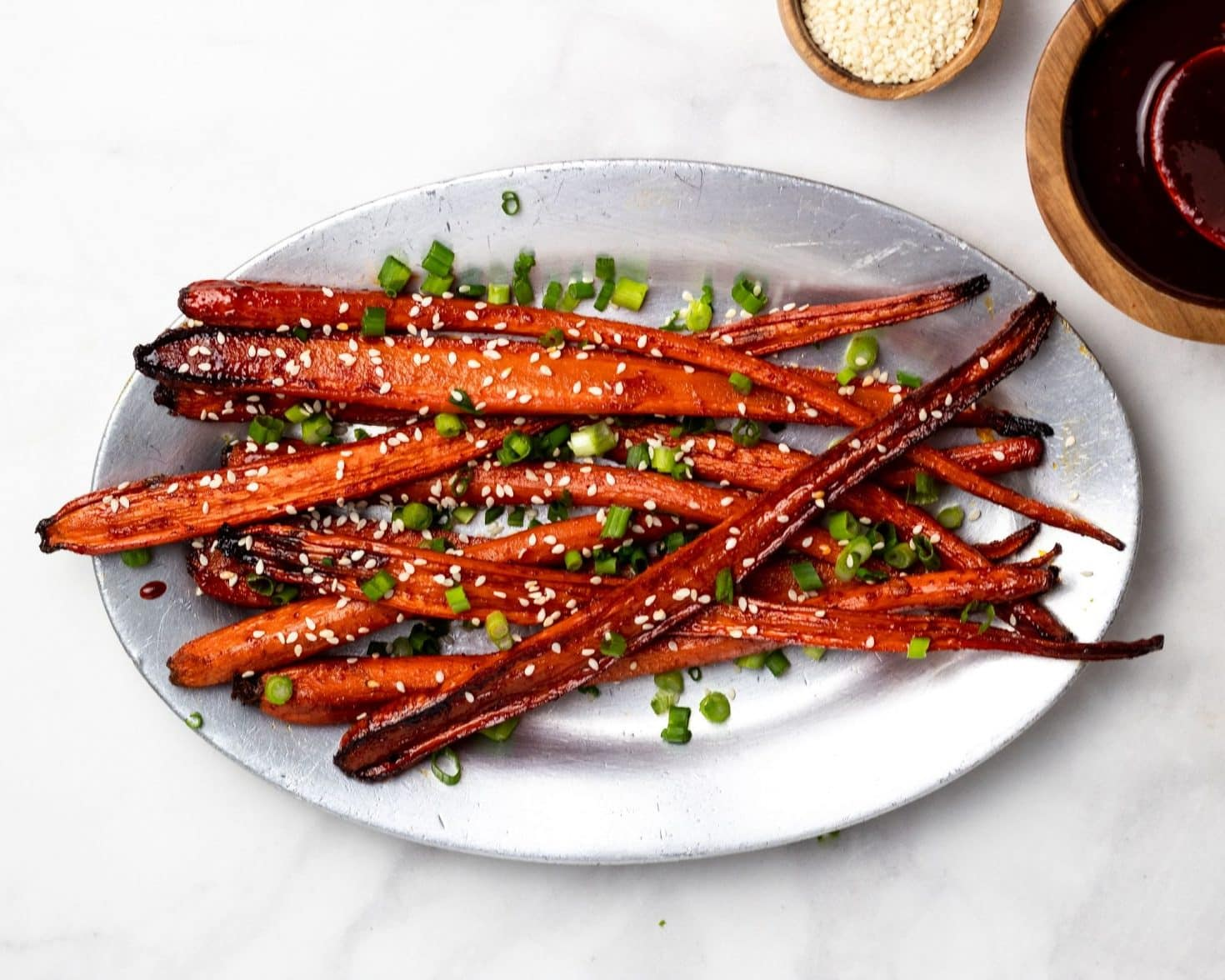 silver plater with gochujang roasted carrots, sesame seeds, scallions