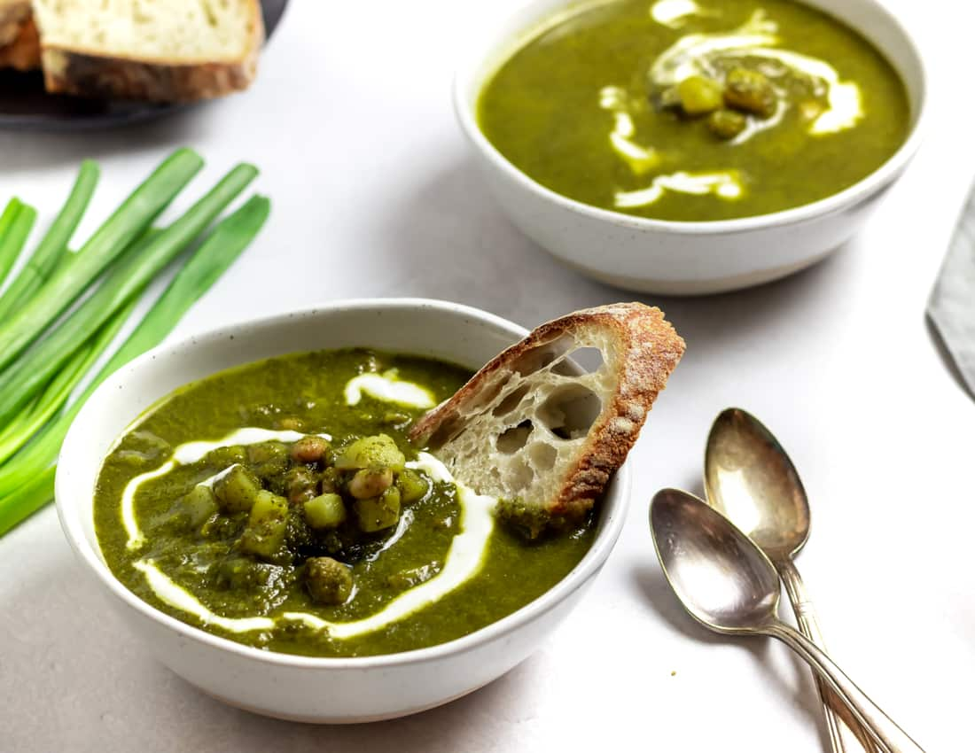 two bowls of winter green goddess soup with bread, scallions, and two spoons
