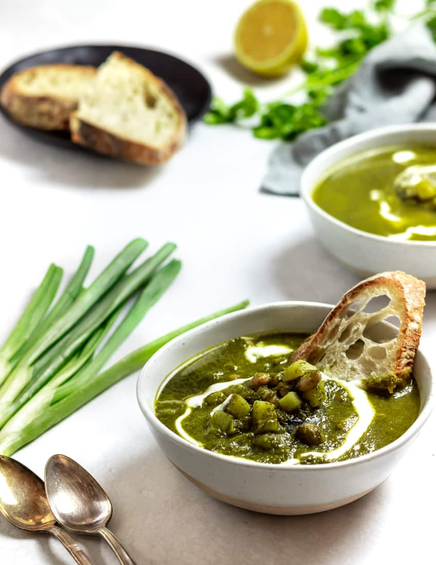 two bowls of winter green goddess soup with bread, scallions, parsley and lemon on a white background
