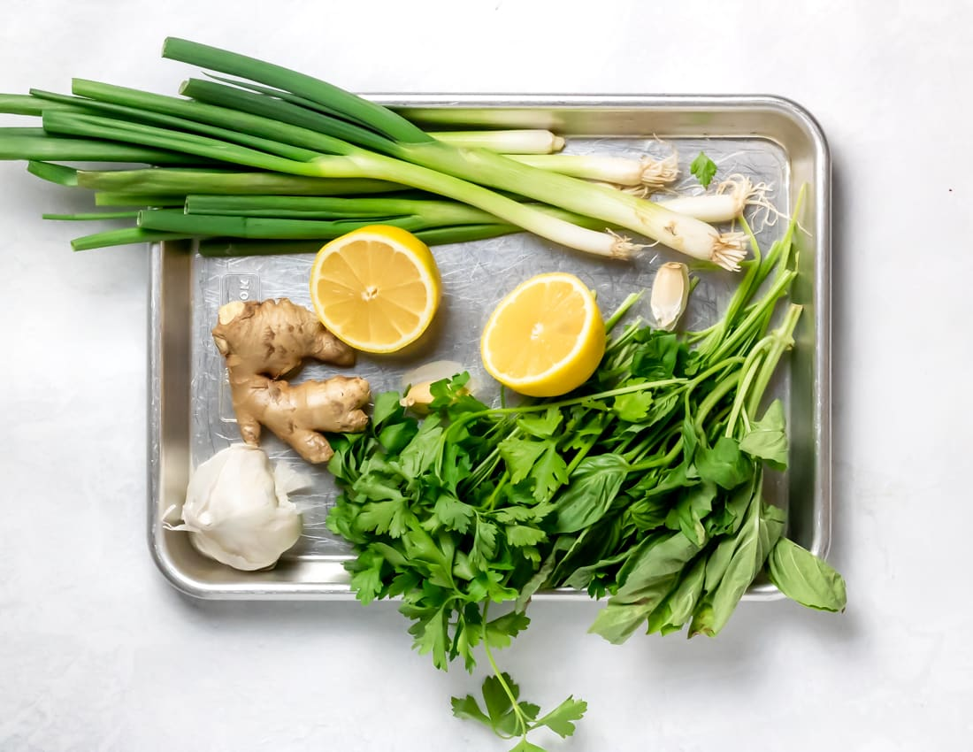 rimmed baking sheet with parsley, scallions, garlic, ginger and lemon on a white background