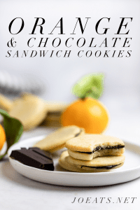 "four chocolate orange sandwich cookies on a white plate with a piece of chocolate and small oranges in the background with text overlay that reads ""Orange & Chocolate Sandwich Cookies"" and ""Joeats.net"""
