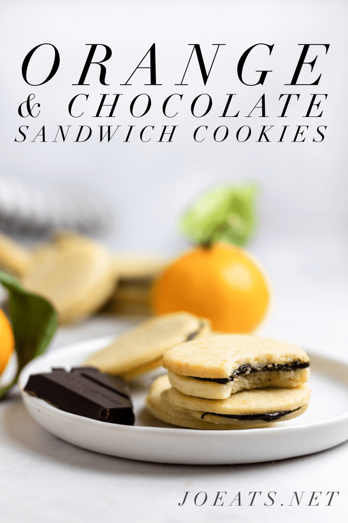 """four chocolate orange sandwich cookies on a white plate with a piece of chocolate and small oranges in the background with text overlay that reads """"Orange & Chocolate Sandwich Cookies"""" and """"Joeats.net"""""""
