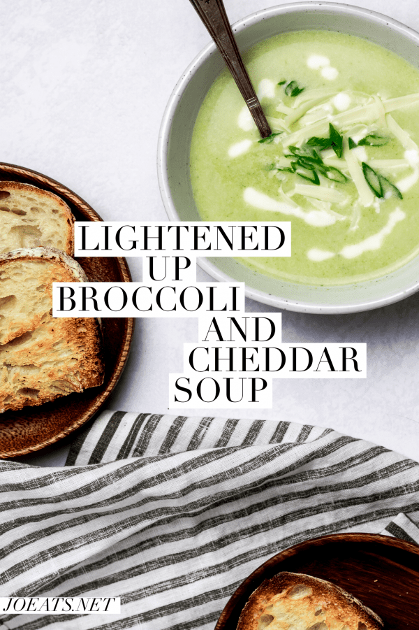 """Overhead shot of broccoli and cheddar soup with bread and a striped napkin and text overlay - """"lightened up broccoli and cheddar soup"""""""