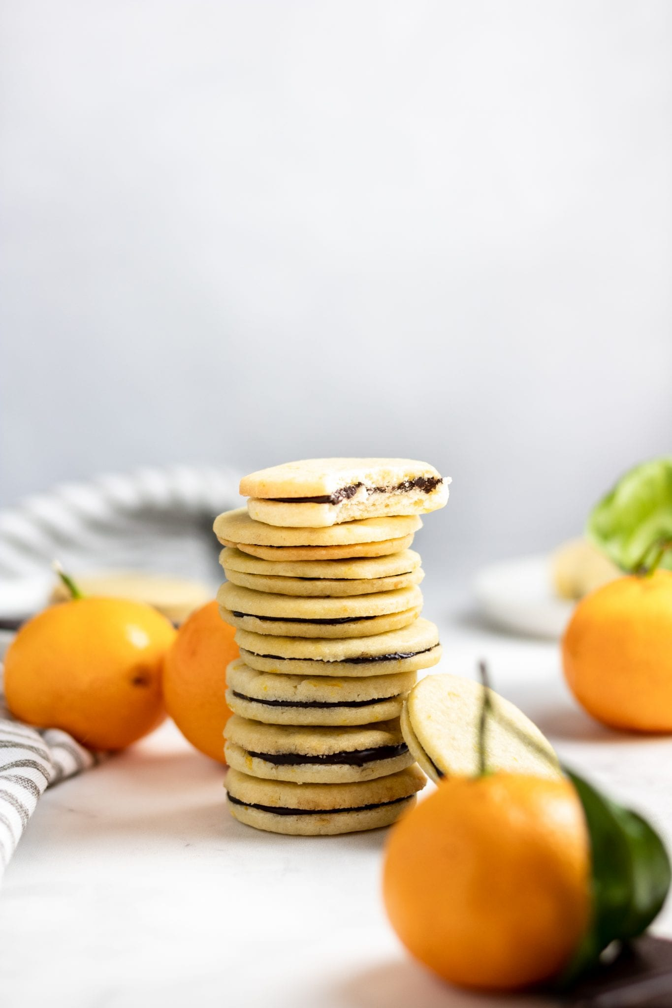 a stack of orange chocolate sandwich cookies with small oranges on a light background