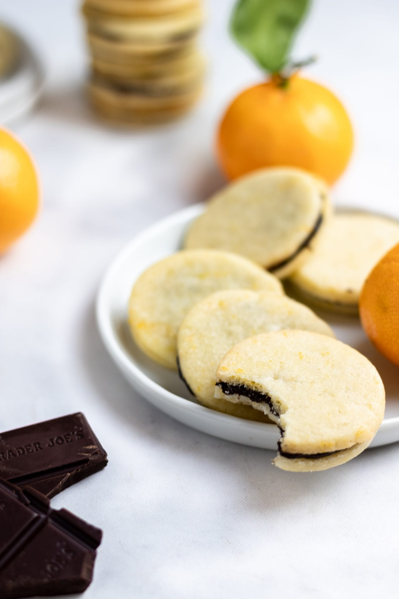 five chocolate orange sandwich cookies on a white plate with a piece of chocolate and small oranges in the background
