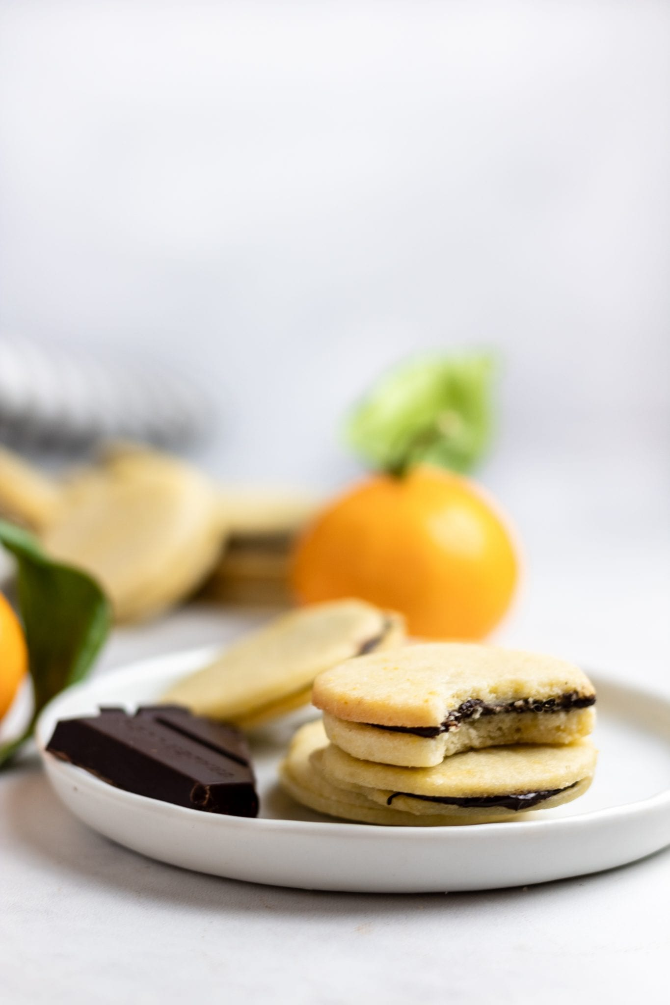 four chocolate orange sandwich cookies on a white plate with a piece of chocolate and small oranges in the background