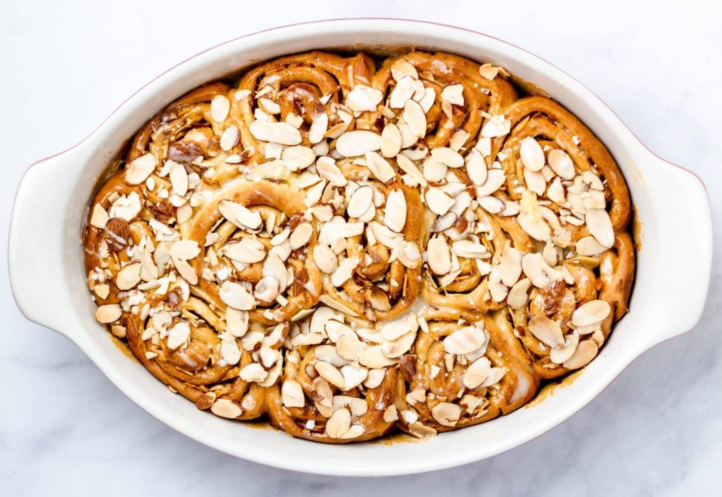 overhead of orange almond breakfast buns in an oval dish