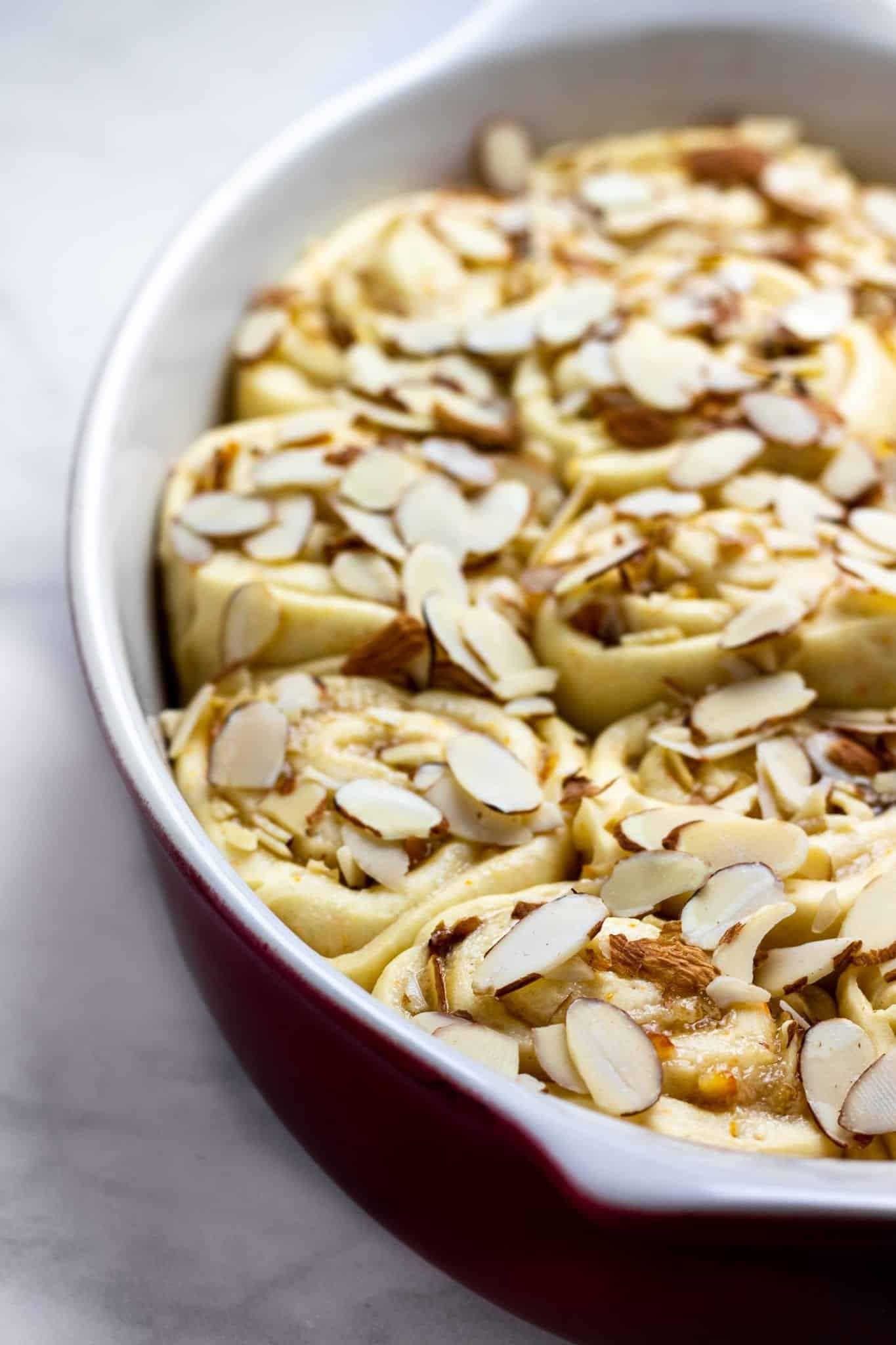 orange almond breakfast buns in an oval dish, unbaked