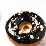 close up of one baked peanut butter donut with chocolate glaze and chopped peanuts