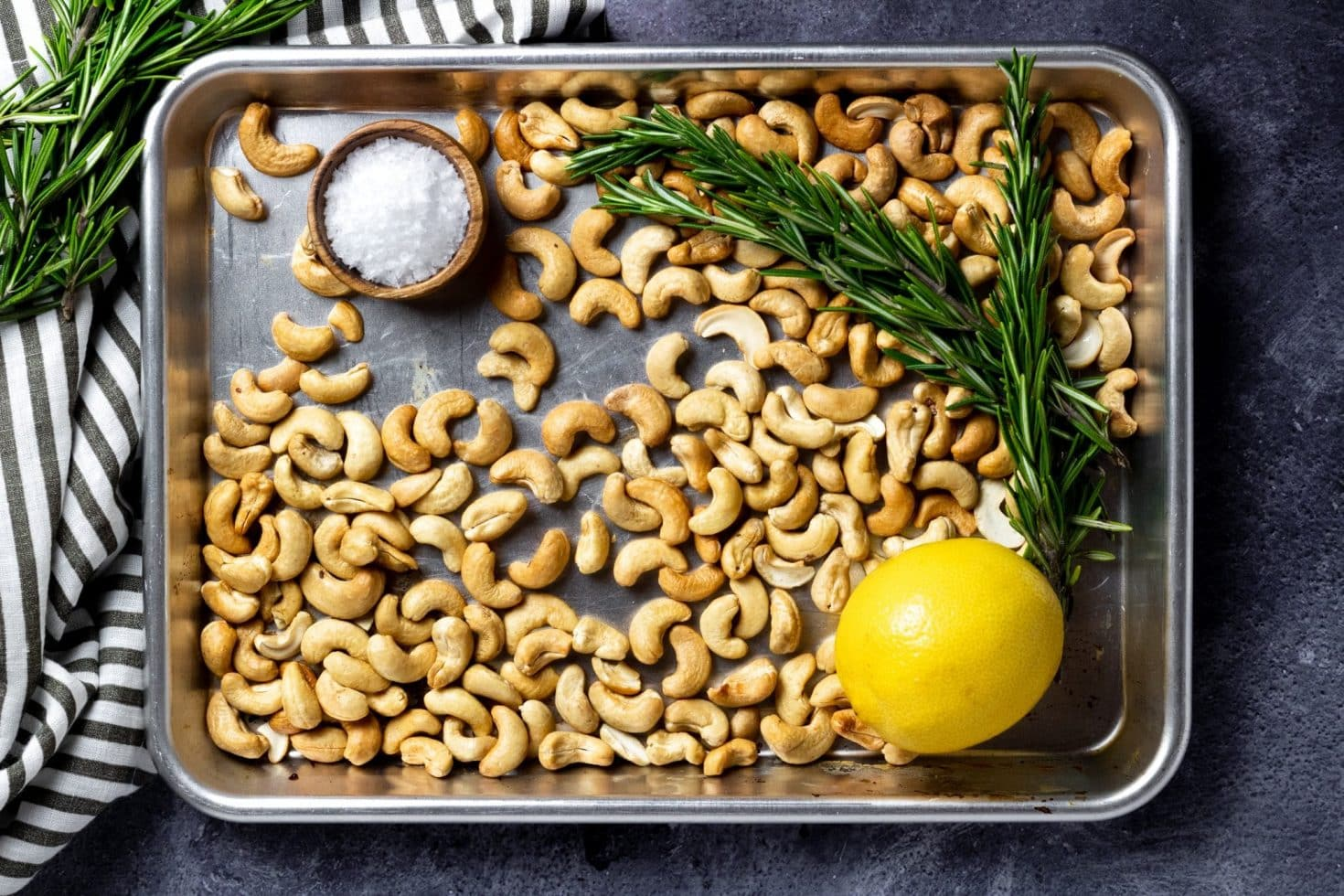 baking sheet with cashews, rosemary, a wooden bowl with flaky sea salt, and a lemon.