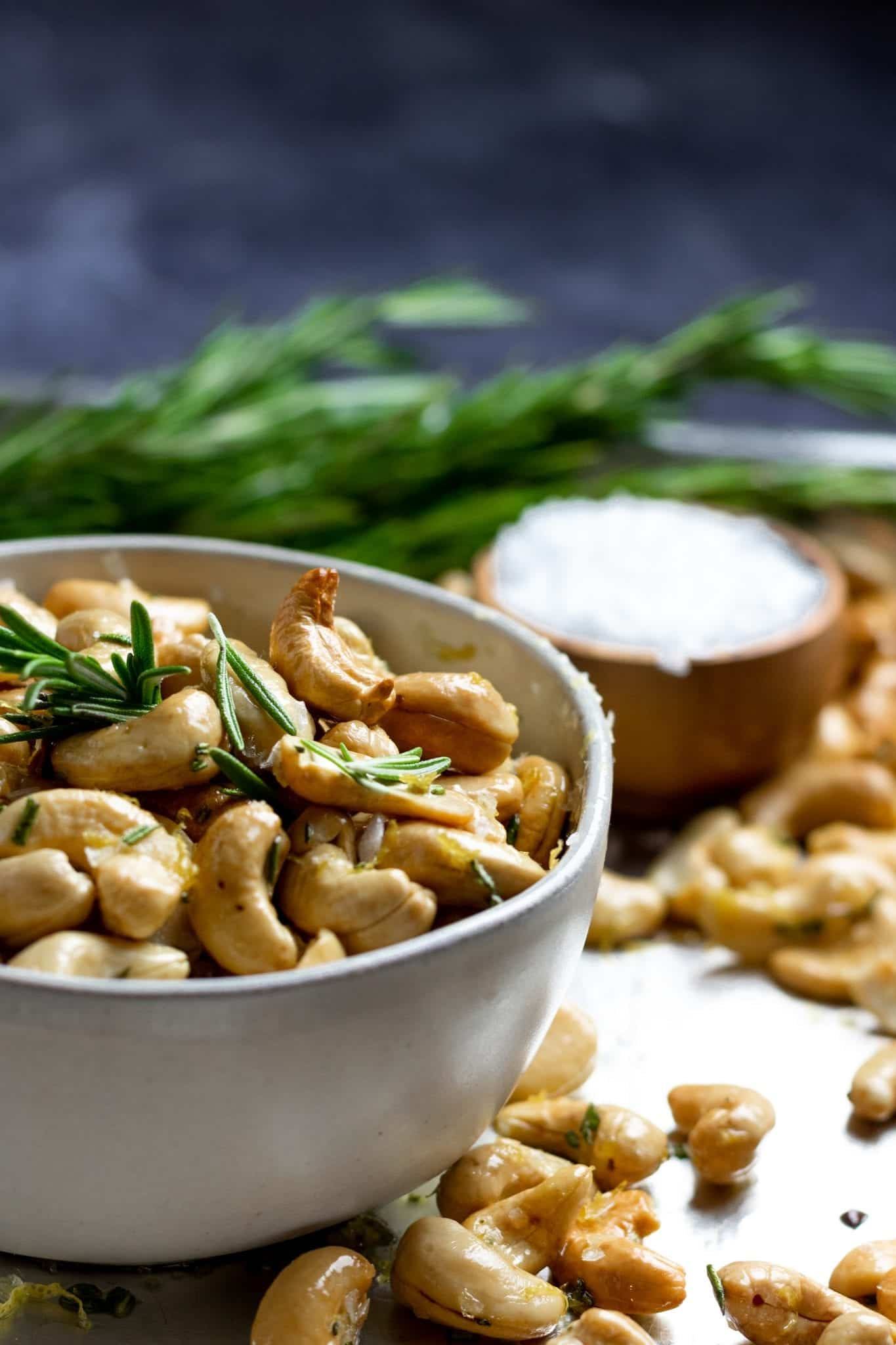 close up of a bowl of rosemary lemon cashews with salt and rosemary in the background