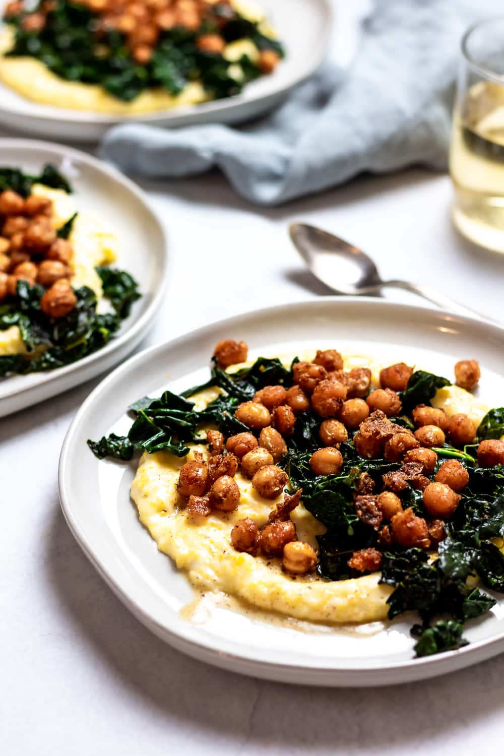 three plates of brown butter spiced chickpeas with kale and polenta