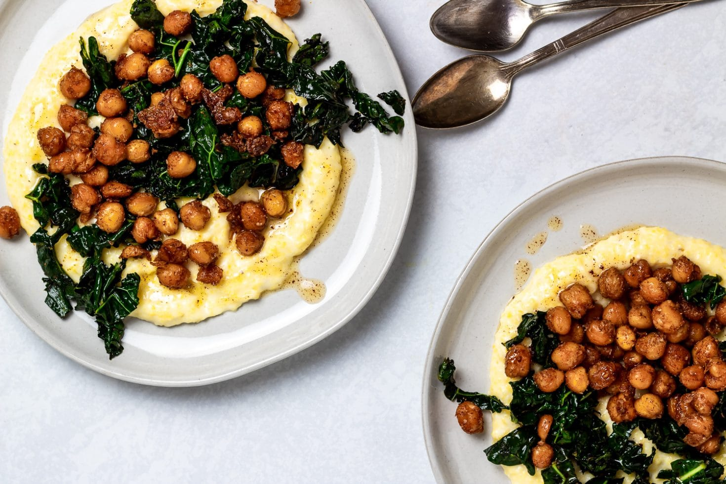 two plates of brown butter spiced chickpeas with kale and polenta