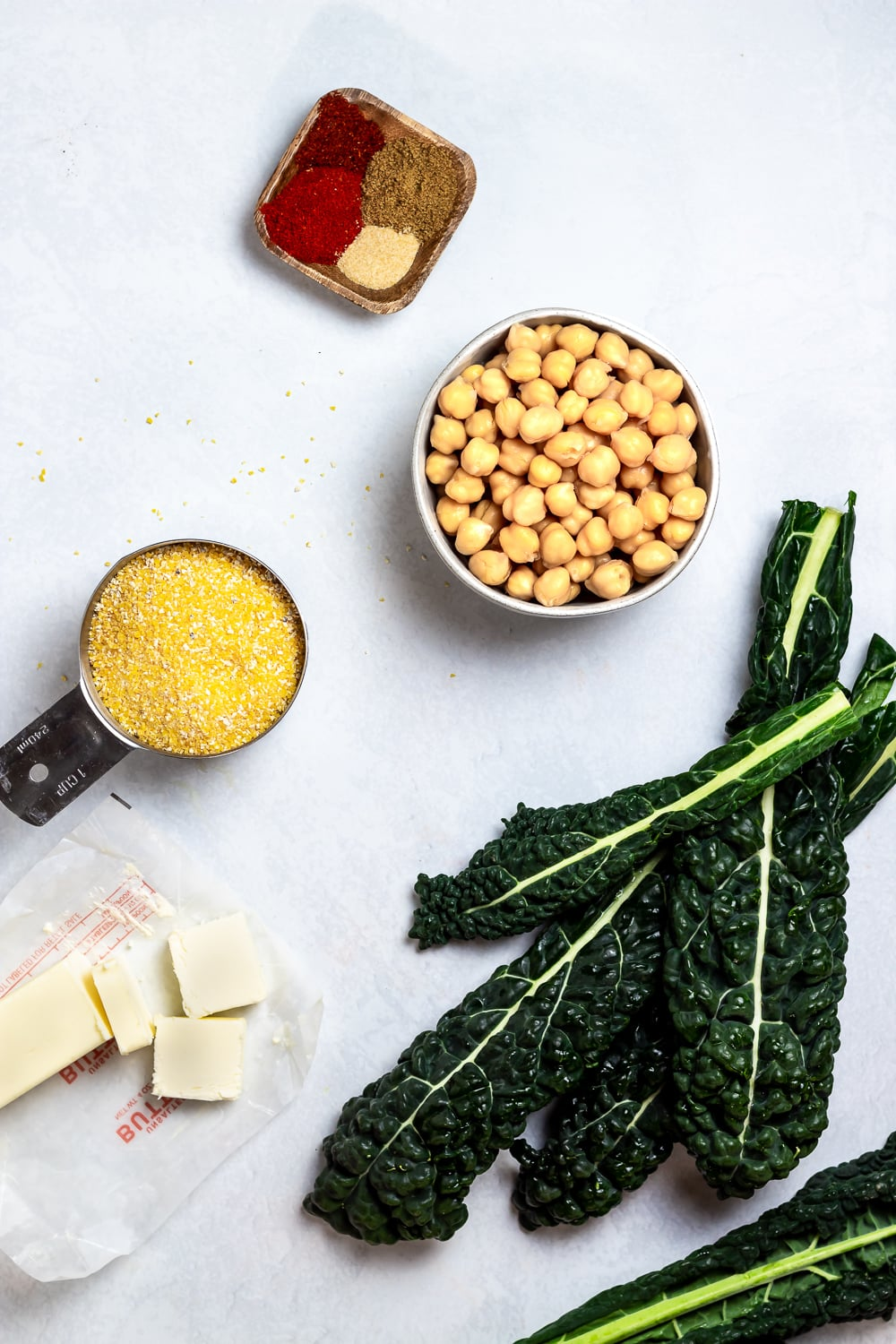 kale, uncooked polenta in a measuring cup, butter cut into pats, chickpeas, and assorted spices on a light grey background