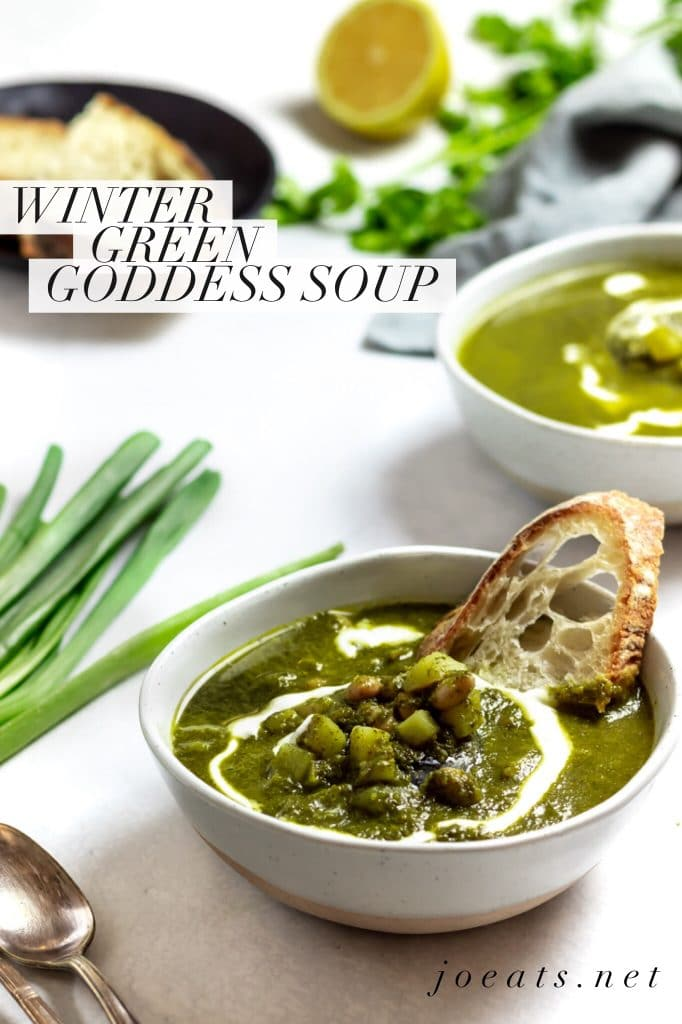 """two bowls of winter green goddess soup with bread, scallions, parsley and lemon on a white background and text overlay that reads """"winter green goddess soup"""" and """"joeats.net"""""""