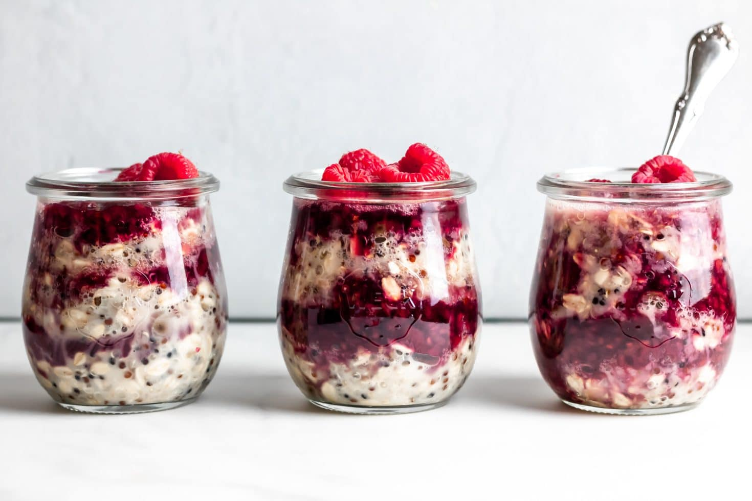 three glass jars of chocolate and raspberry quinoa overnight oats, one with a silver spoon