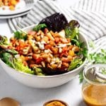 white bowl with roasted root vegetable salad, striped napkin, white plate with salad in background, turmeric honey dressing in a glass jar, wooden spoon, and small wooden bowl with turmeric