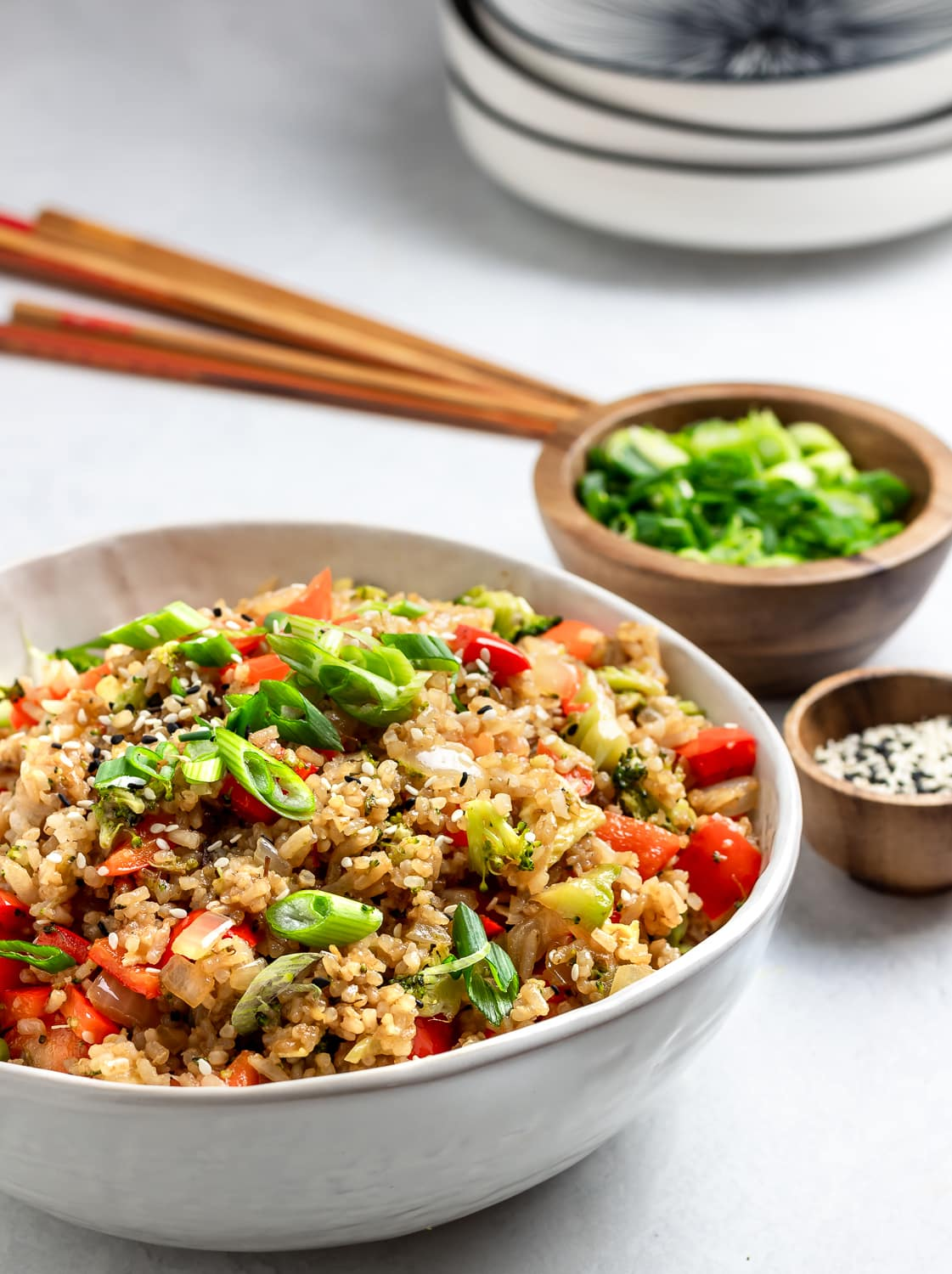 fried rice in a white bowl with scallions and sesame seeds and chop sticks