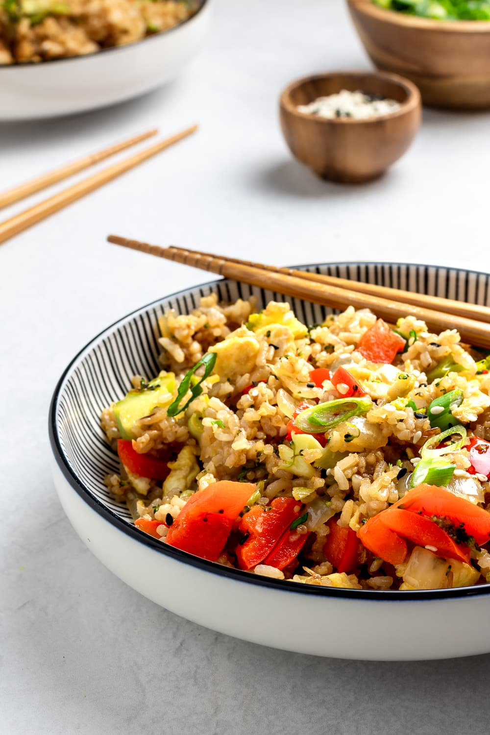 veggie fried rice in a striped bowl with chopsticks