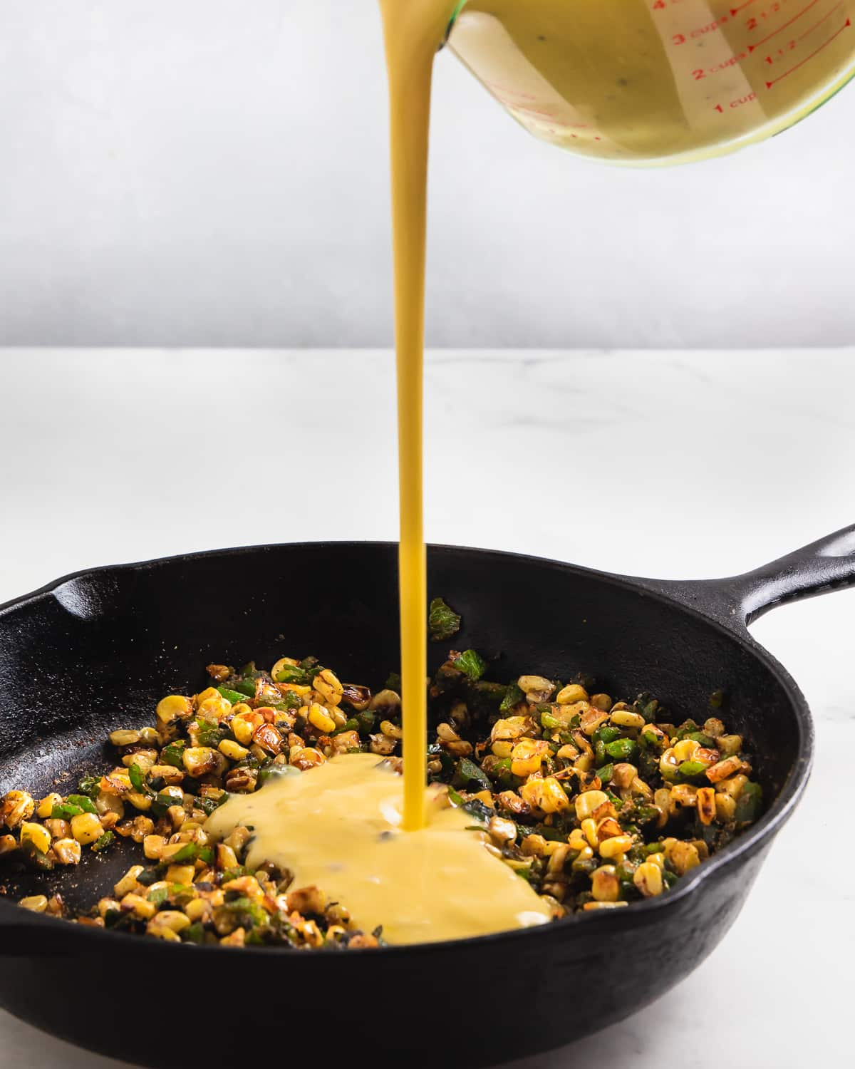 cast iron skillet with charred corn and poblano peppers, pouring egg mixture in from a glass measuring cup