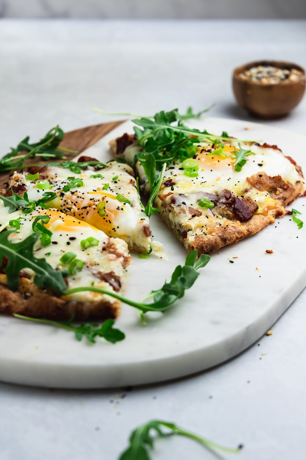 marble and wood board with sliced flatbread brunch pizza with runny egg, arugula, and small wood bowl with spices in the background