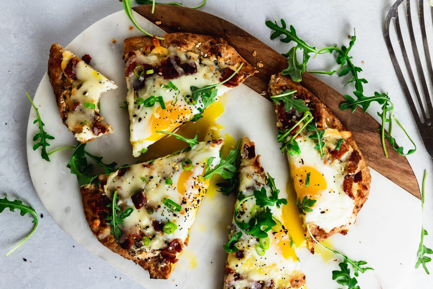 marble and wood board with sliced breakfast pizza with runny egg, arugula, and thin metal spatula