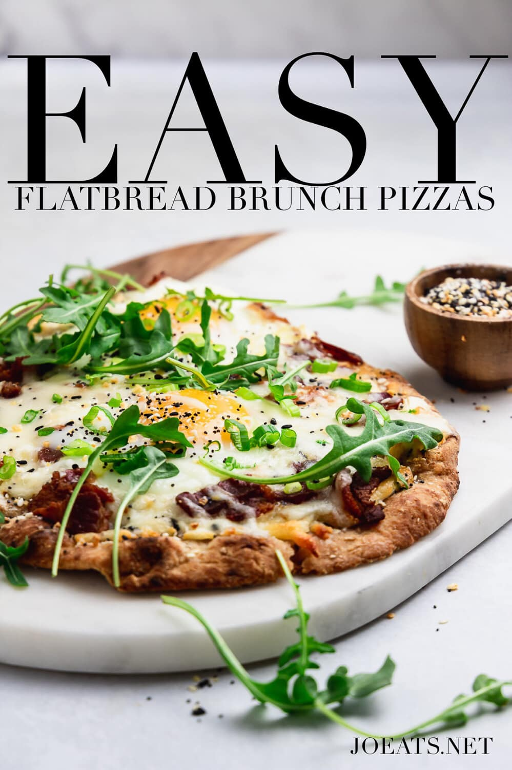 "marble and wood board with flatbread brunch pizza with runny egg, arugula with text overlay that reads ""easy flatbread brunch pizzas"" and ""joeats.net"""