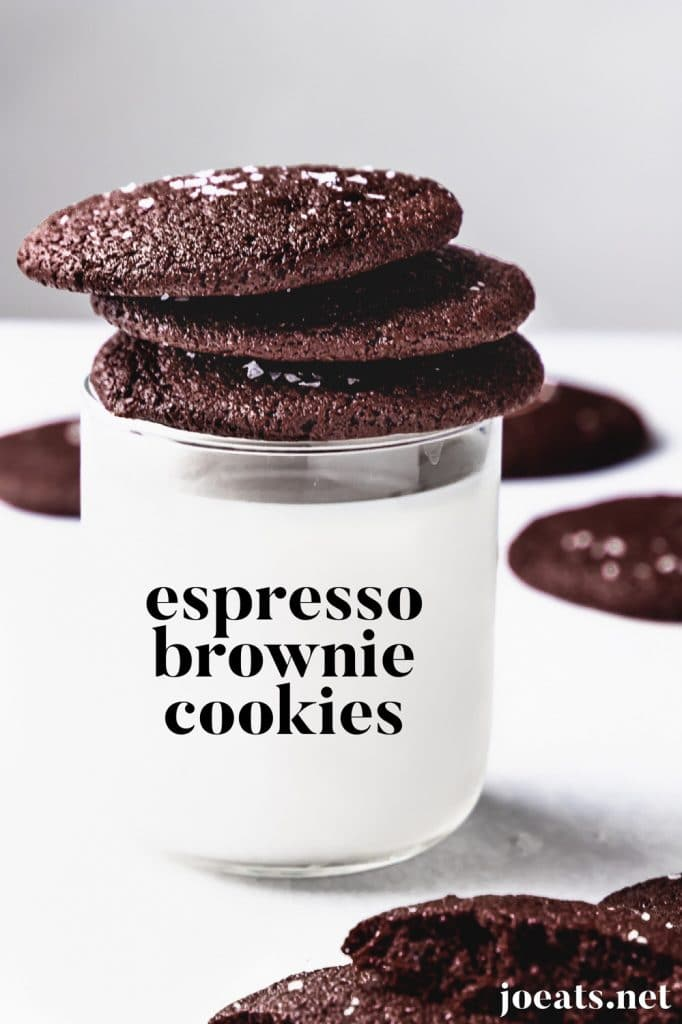 """stack of espresso brownie cookes with flaky sea salt on white background with glass of milk with text that reads """"espresso brownie cookies"""""""