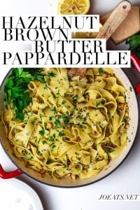 "overhead of large pan of wide noodles with parsley, lemon, parsley, hazelnuts and butter with text overlay that reads ""hazelnut brown butter pappardelle"" and ""joeats.net"""