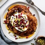 overhead shot of a plate of whole grain pancakes with yogurt, pomegranate seeds, pumpkin seeds, maple syrup, butter, and a blue napkin