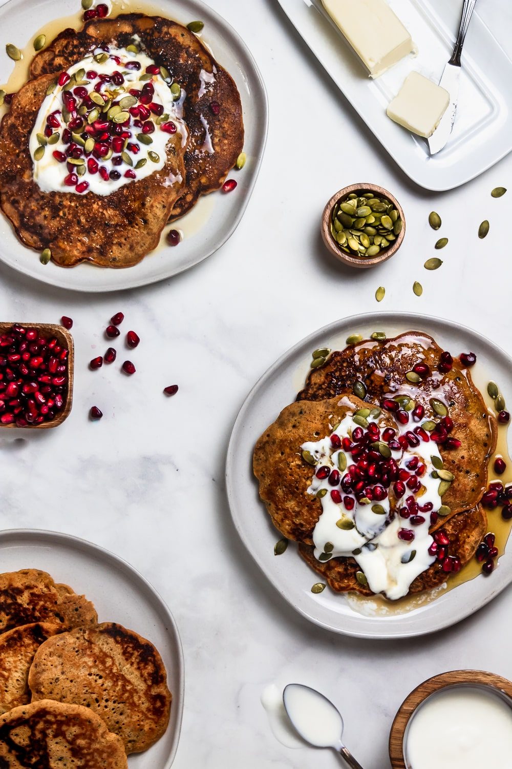 overhead shot of three plates of whole grain pancakes with yogurt, pomegranate seeds, pumpkin seeds, and butter