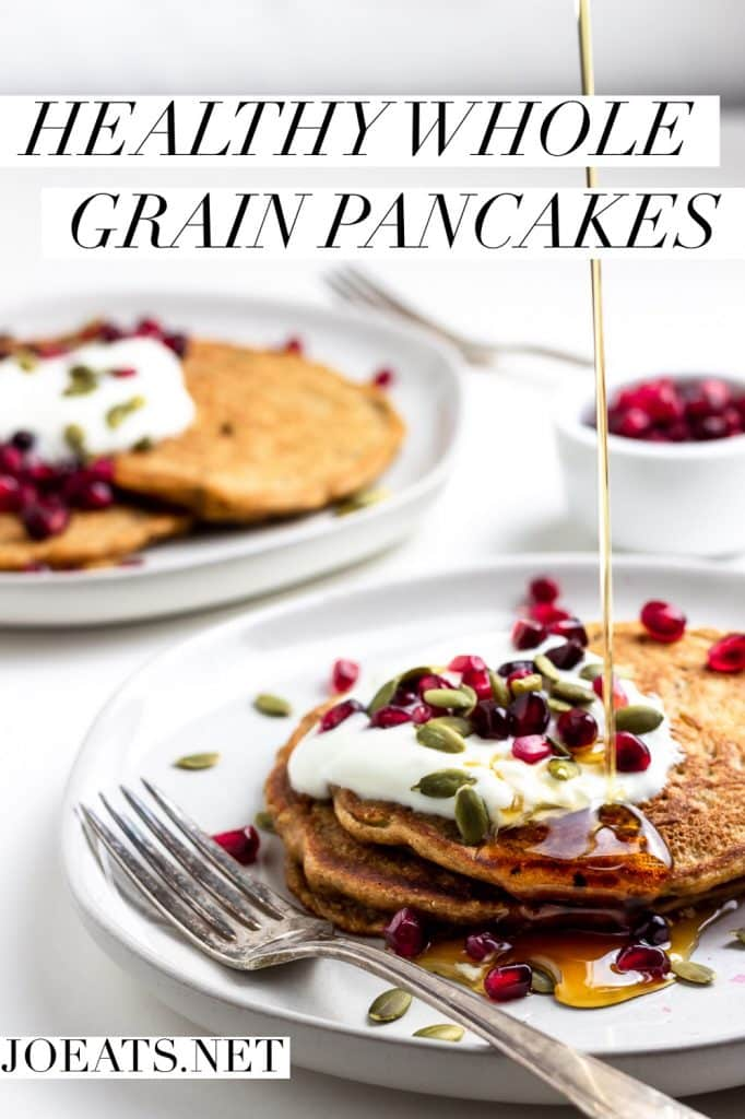"""healthy whole grain pancakes on white plates with pomegranates, pumpkin seeds, whole milk yogurt, and a drizzle of maple syrup with text overlay that reads """"healthy whole grain pancakes"""" and """"joeats"""""""